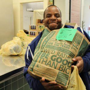 Man holding bag of groceries for Thanksgiving dinner
