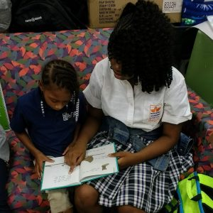 first grader reading with her middle school mentor