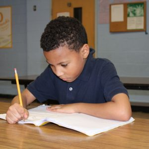 Kaden, a boy in fourth grade, completes his math homework.